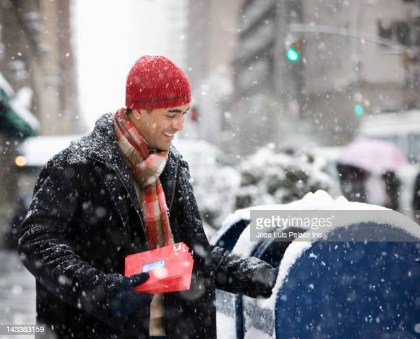man mailing christmas cards in city - sending stock photos and pictures