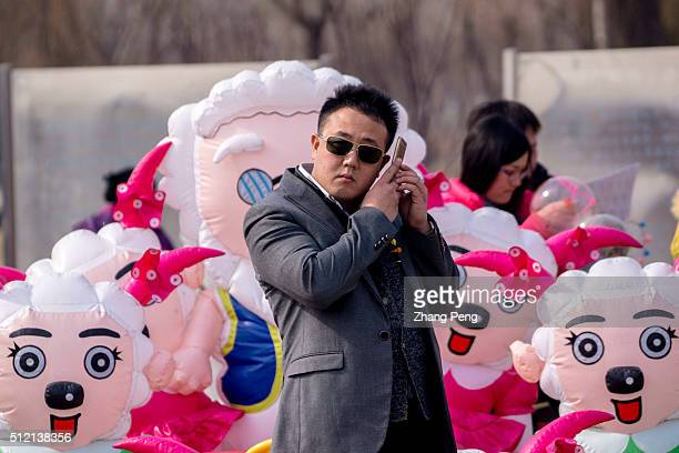 A man make a mobile phone call in front of a weird plastic toy car decorated by copycat Pleasant Goats This weird plastic toy cars decorated of all...