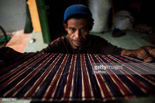 A man make handicraft weaving in Gemplong Yogyakarta Indonesia on Auguts 3 2016 The weaving craft can be made tablecloths bags and slippers with a...