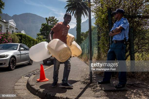 A man make his way past a police officer on duty at the Newlands spring tap on their way to refill water bottles at one of many fresh mountain spring...