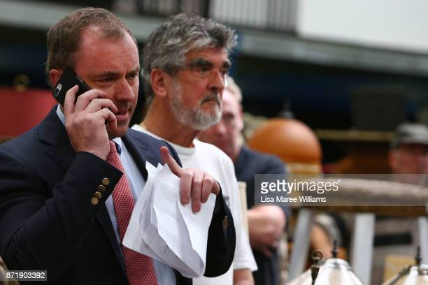 A man makes a bid on behalf of a phone client during the auction of the 2000 Olympic Gold Medal won by Michael Diamond on November 9 2017 in Sydney...