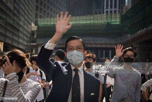 A man makes a gesture about the 5 demands during a march Thousands of office workers and masked protesters clash with police in one of the most...