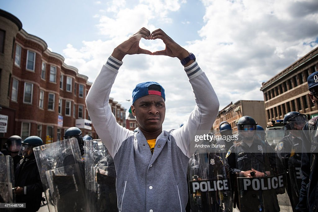 A man makes a heart shape with his hands during a protest near the CVS pharmacy that was set on fire yesterday during rioting after the funeral of Freddie Gray, on April 28, 2015 in Baltimore, Maryland. Gray, 25, was arrested for possessing a switch blade knife April 12 outside the Gilmor Houses housing project on Baltimore's west side. According to his attorney, Gray died a week later in the hospital from a severe spinal cord injury he received while in police custody.