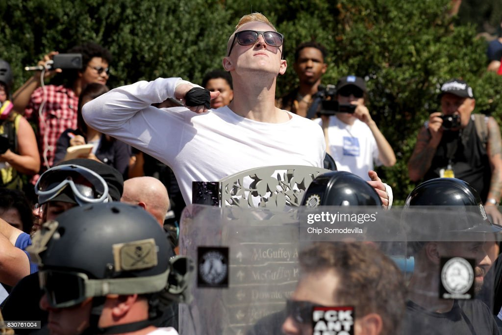 A man makes a slashing motion across his throat twoard counter-protesters as he marches with other white nationalists, neo-Nazis and members of the 'alt-right' during the 'Unite the Right' rally August 12, 2017 in Charlottesville, Virginia. After clashes with anti-fascist protesters and police the rally was declared an unlawful gathering and people were forced out of Emancipation Park, where a statue of Confederate General Robert E. Lee is slated to be removed.