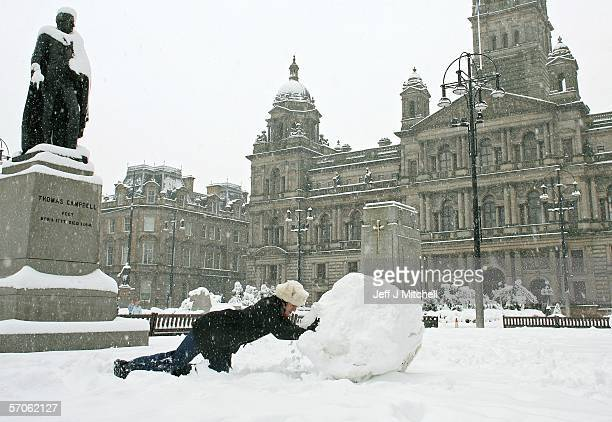 A man makes a snowman at George Square after cold weather brought heavy snowfalls overnight on March 12 2006 in Glasgow Scotland Scotlands two main...