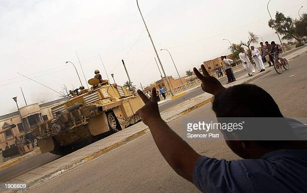 Man makes a victory sign to a British tank after they occupied most of the strategic southern Iraqi city from Saddam Hussein loyalists April 8, 2003...