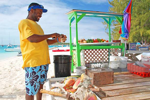 man makes conch salad on bahamas beach - conch shell stock pictures, royalty-free photos & images