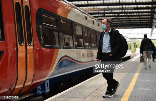 Man makes his way onto a East Midlands Trains at Stoke-on-Trent Train Station on May 20, 2021 in Stoke, England. The British government has created a...