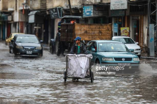 A man makes his way through a flooded street caused by rainfall in Gaza City Gaza on November 26 2020