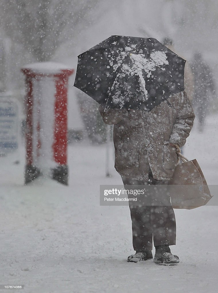 A man makes his way through a snow blizzard on December 18, 2010 in West Ewell, England. The United Kingdom is continuing to suffer heavy snowfall causing misery for travellers as it was warned there would be severe disruption to all London airports after British Airways cancelled all flights out of Heathrow until 17:00 GMT today and flights out of Gatwick between 10:00 and 16:00GMT.