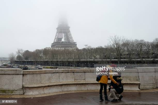 A man makes his wedding proposal on Valentine's day not far from the Eiffel tower on a foggy day on February 14 2018 in Paris / AFP PHOTO / Ludovic...