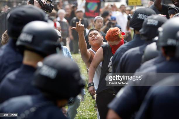 A man makes obscene gestures as police break up rockthrowing antineoNazi demonstrators after a National Socialist Movement rally near City Hall on...