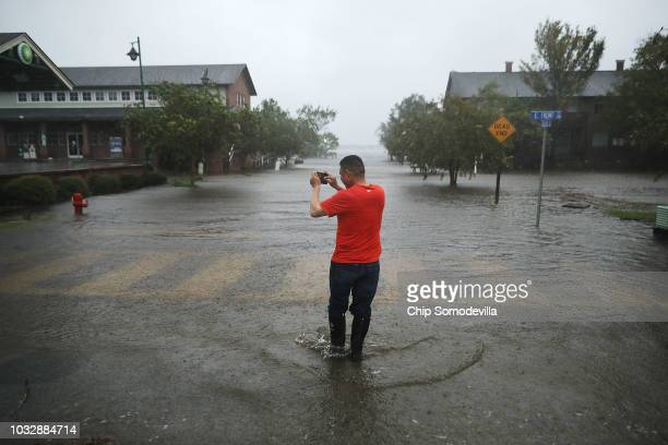 A man makes photographs of the flooded streets as the Neuse River floods its banks during Hurricane Florence September 13 2018 in New Bern North...