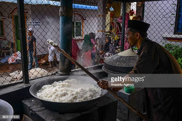 A man makes rice as sacrificial cows were prepared outside the prayer hall during EidAlAdha in Phnom Penh Cambodia on Monday September 12 2016