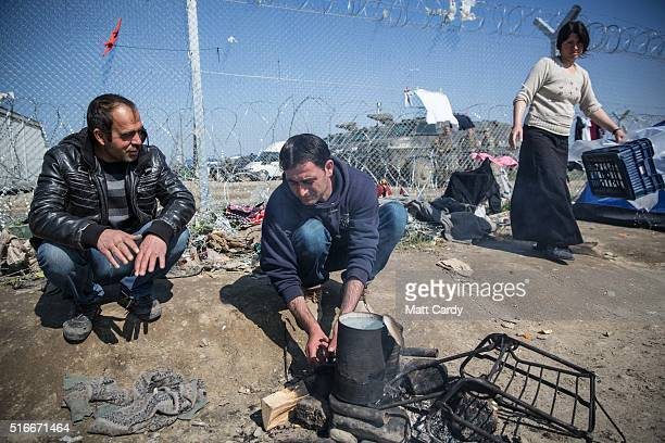 A man makes tea in front of the border fence at the Idomeni refugee camp on the Greek Macedonia border on March 20 2016 in Idomeni Greece Thousands...