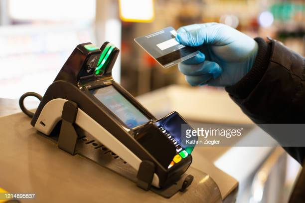 man making a cashless payment at supermarket, wearing protective gloves - contactless payment stock pictures, royalty-free photos & images