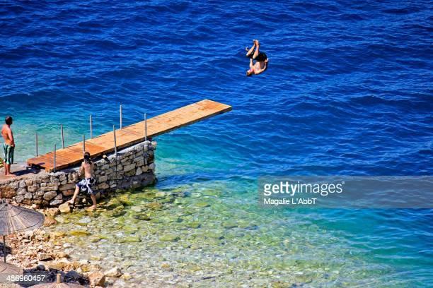 Man making a flip jump into the sea
