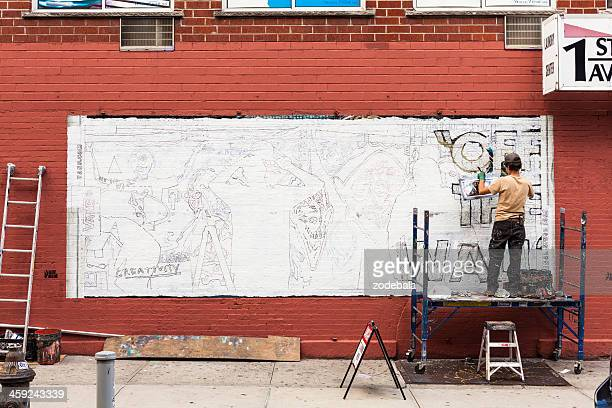 man making a graffiti on the wall - mural stock pictures, royalty-free photos & images