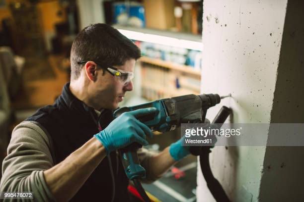 man making a hole in the wall with a drill - drill stock pictures, royalty-free photos & images