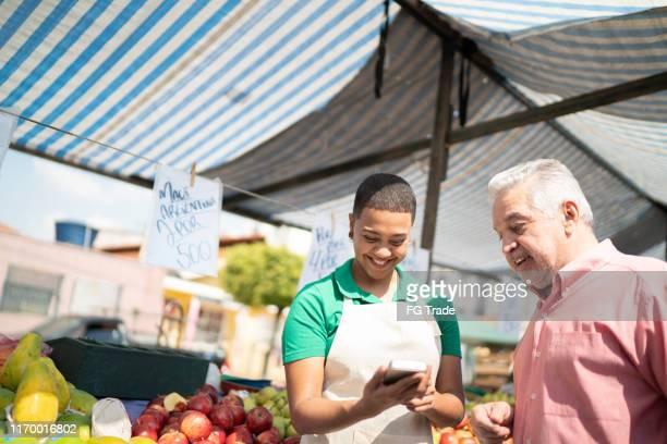homem que faz um pagamento usando o cartão de crédito em um mercado de rua - acessibilidade - fotografias e filmes do acervo