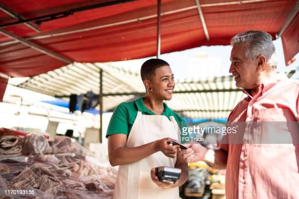 homem que faz um pagamento usando o cartão de crédito em um mercado de rua - ciência e tecnologia - fotografias e filmes do acervo