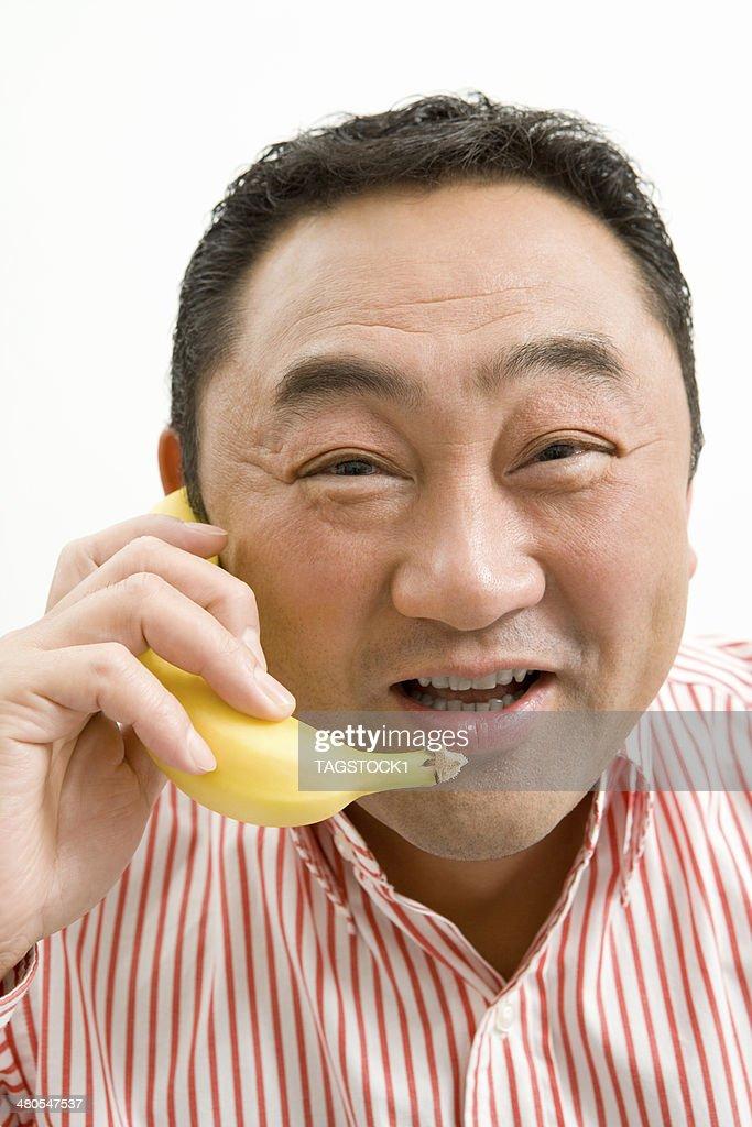 Mann macht einen Anruf mit Banane : Stock-Foto