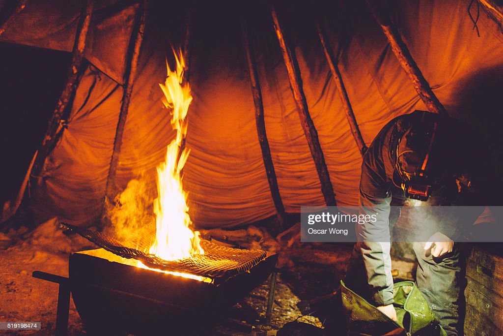 Man making c& fire in tent  Stock Photo & Man Making Camp Fire In Tent Stock Photo | Getty Images