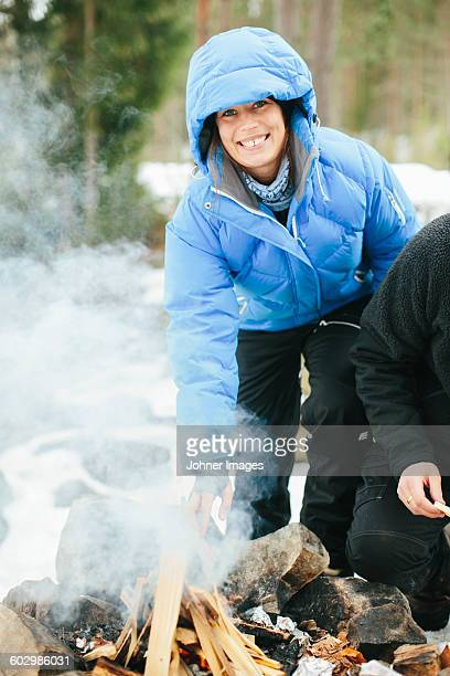 Man making campfire, woman looking at camera