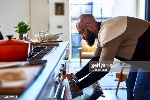 man making dinner and opening oven - men stock pictures, royalty-free photos & images