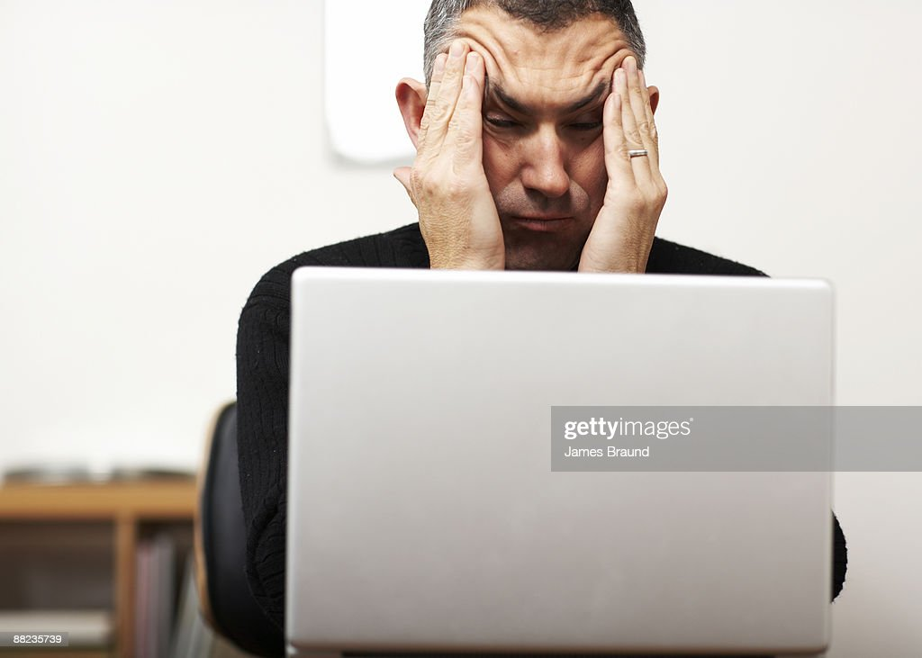 Man making faces from behind laptop : Stock Photo