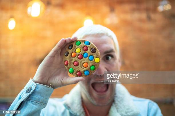 man making faces holding a chocolate chip cookie - comfort food stock pictures, royalty-free photos & images