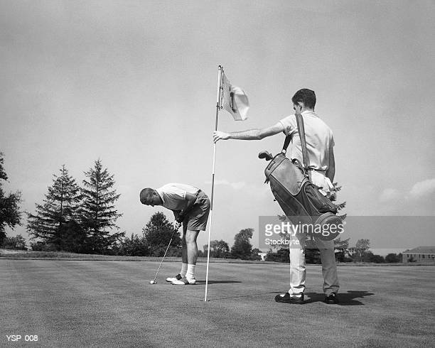 Hombre de la foto caddie de golf mientras está bandera de retención
