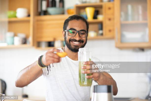 man making green juice in kitchen - sigrid gombert stock pictures, royalty-free photos & images