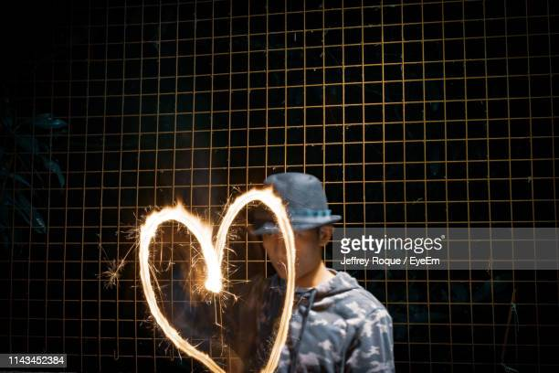 man making heart shape with sparkler while standing against metal fence - jeffrey roque stock photos and pictures