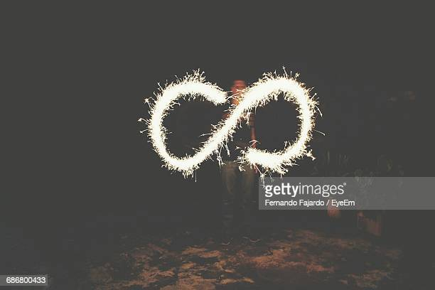 Man Making Infinity Light Painting With Sparkler At Night