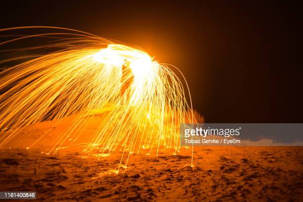 Man Making Light Painting On Sand Against Sky At Night