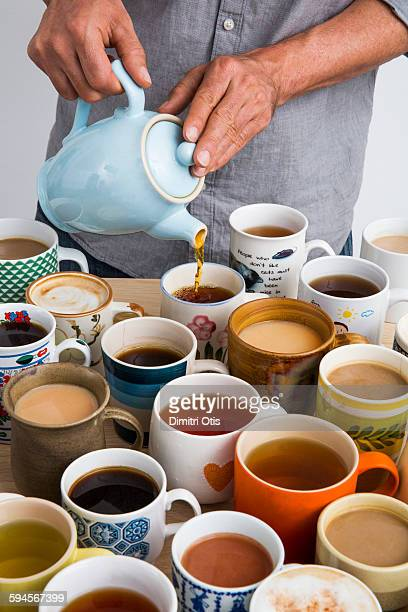 Man making many cups of tea and coffee