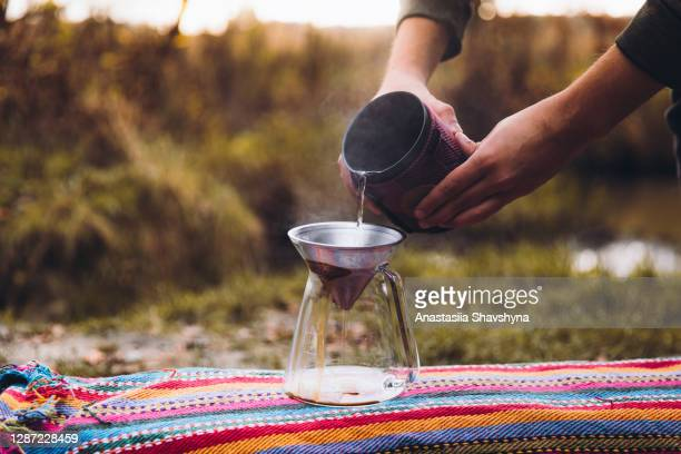 man making morning coffee outdoors by the lake - windbreak stock pictures, royalty-free photos & images