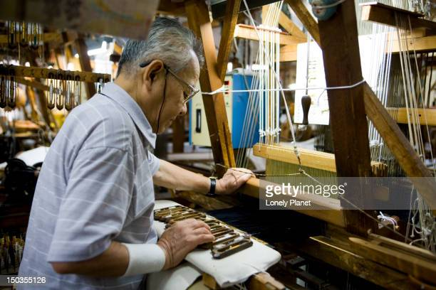 Man making obi (a silk sash to hold kimono) on a hand loom.