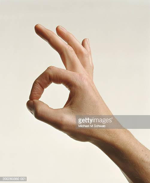 Man making 'ok' sign, side view, close-up of hand