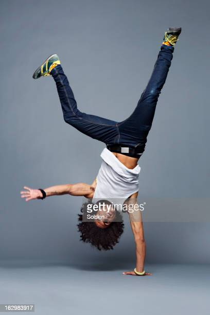 man making one arm handstand, studio background - op z'n kop stockfoto's en -beelden