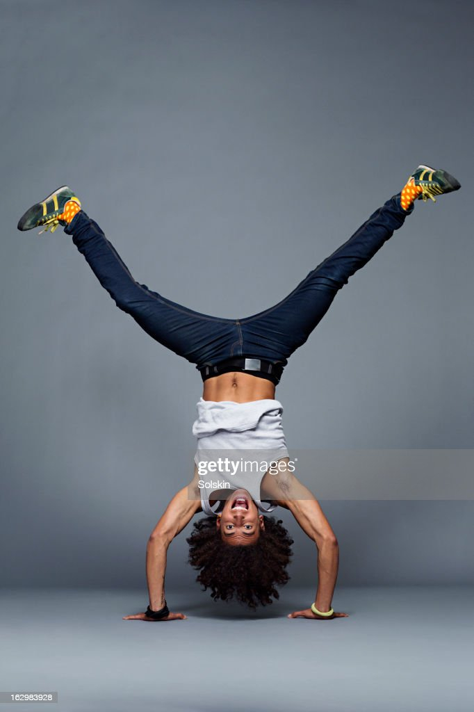 Man making one arm handstand, studio background : Stock Photo