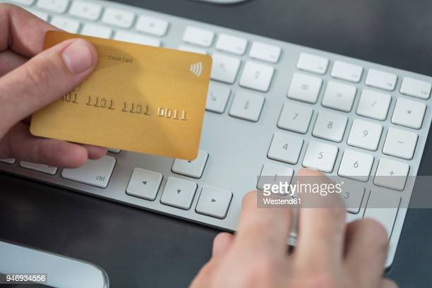 Man making online payment with credit card at desk, close-up