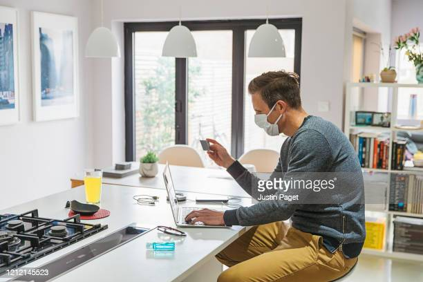 man making online purchase whilst working from home - consumerism stock pictures, royalty-free photos & images