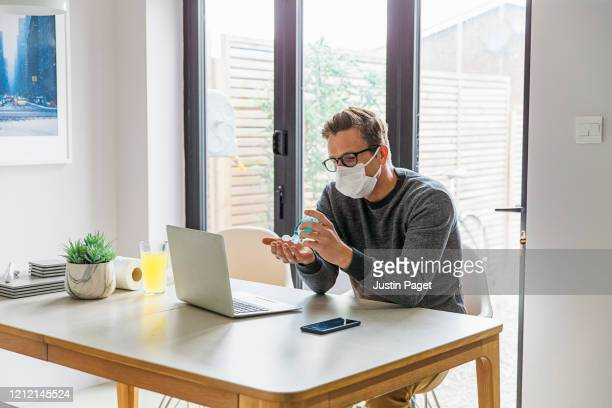 man making online purchase whilst working from home - social distancing stock pictures, royalty-free photos & images