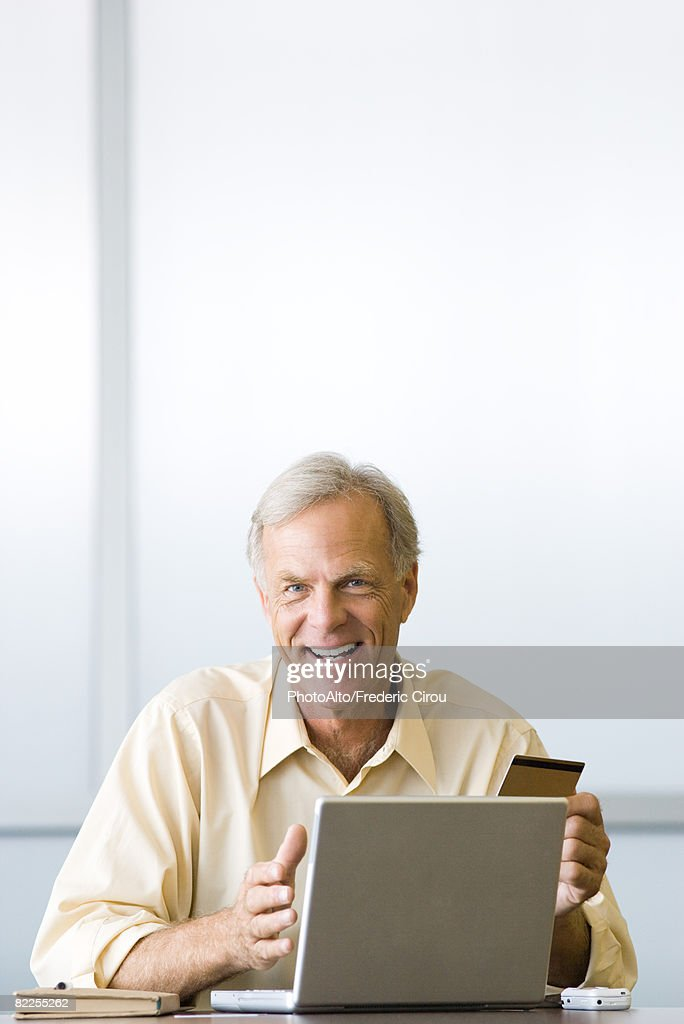 Man making on-line purchase with credit card, smiling at camera : Stock Photo