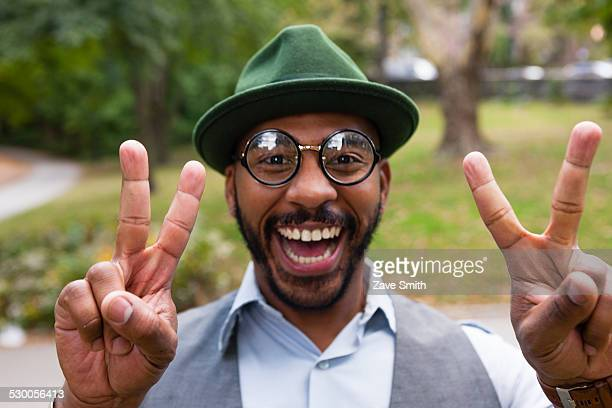 man making peace sign smiling widely in park - peace symbol stock photos and pictures