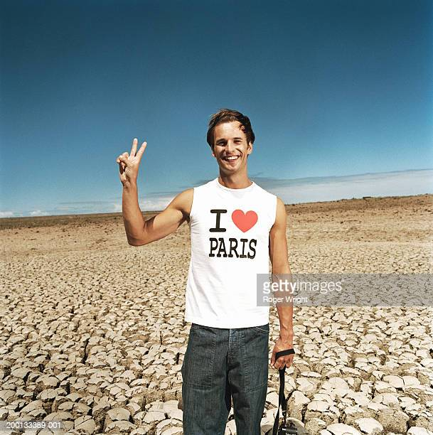 Man making peace sign, standing on cracked ground, portrait