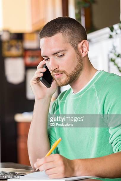 Homme faisant appel téléphonique pour régler la facture du bureau