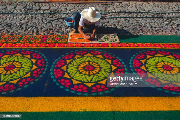 man making rangoli on footpath - rangoli stock pictures, royalty-free photos & images